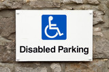 disabled parking sign on stone wall