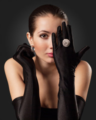Glamorous Woman in Black Gloves with a Circular Ring