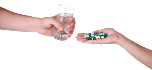 Headache hand with pills medicine tablets and glass of water aga