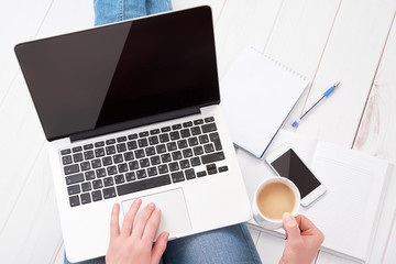 happy young woman  relaxes and  working at home at a laptop with