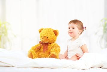 cute little child girl hugging teddy bear in bed