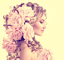 Beauty girl with rose flowers hairstyle. Long permed curly hair