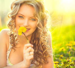 Beauty blond model girl smelling dandelion flower