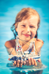 Happy child holding toy sailing boat in hands