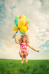 Child with toy balloons in spring field