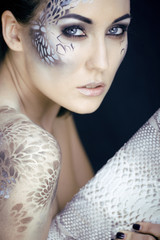 fashion portrait of pretty young woman with creative make up lik
