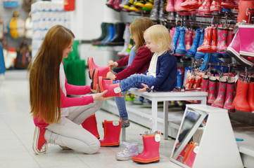 Mother and her two girls choosing new rain boots
