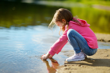 Adorable little girl playing by a river