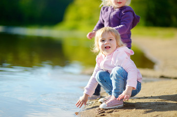 Two adorable little sisters playing by a river