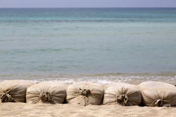 Sacchi di sabbia su sfondo mare