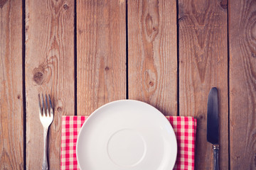 Wooden table with empty plate. View from above