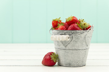 Strawberries, a bucket, a white table and a turquoise background