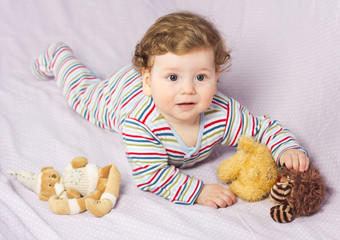 Beautiful child in crib with toys.. Portrait of a baby