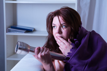 Frightened woman in bed with a torch at night