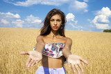 Sexy young happy girl holds hands in a wheat field