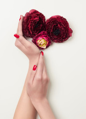 hands with red manicure and red flowers