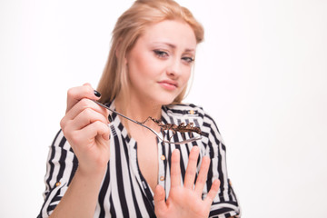 Disgusted woman eating insects with a fork in a restaurant