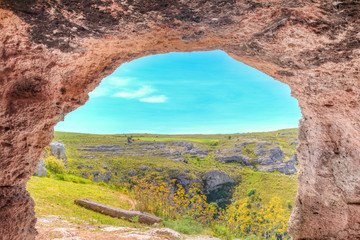 View through cave of tipical vegetation near Matera