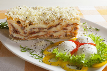Delicious lasagna Bolognese on a plate with garnish.