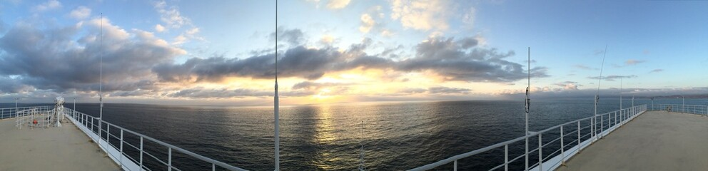 Panorama of sunset over ocean from bow and deck of oceanliner.