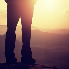 Woman hiker legs in tourist boots stand on mountain rocky peak