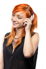Red-haired young girl talking on a smartphone