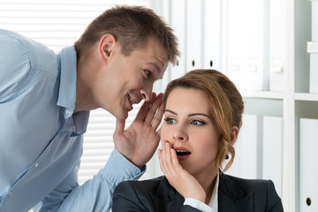 Young man telling gossips to his woman colleague