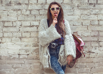 Young street fashion girl on the background of old brick wall