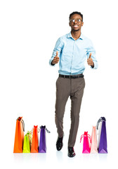 Happy african american man with thumbs up and shopping bags on w