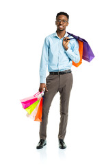 Happy african american man holding shopping bags on white. Holid
