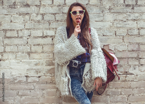 Young street fashion girl on the background of old brick wall - 82708045