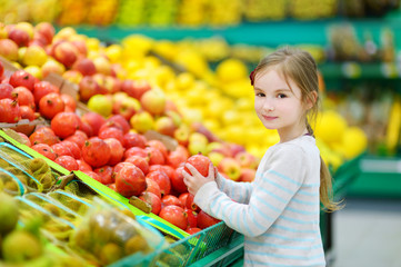 Little girl choosing pomegranate in a food store