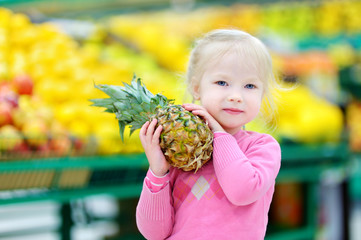 Little girl holding a pineapple in a food store