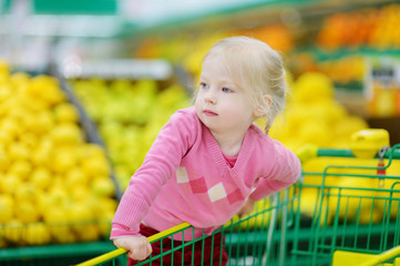 Cute little toddler girl shopping in a food store