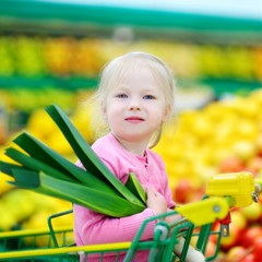 Cute little girl holding a leek in a food store