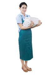 Young maid holding bedding and towels