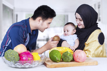 Two parents with their baby and fruits
