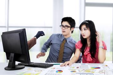 Shocked businesspeople looking hacker 1