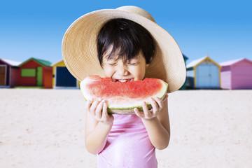Pretty kid eat watermelon at coast