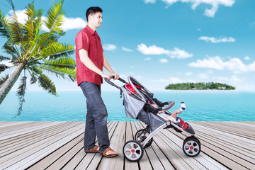 Man with his baby in stroller at pier