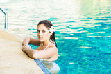 Beautiful woman relaxing in a pool at summer