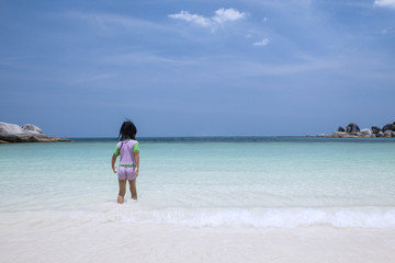 Little girl walking alone at beach
