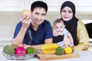 Healthy family with fresh fruits in kitchen