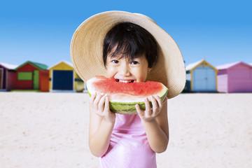 Happy little kid bite a watermelon
