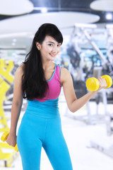 Fitness trainer exercise with two dumbbells
