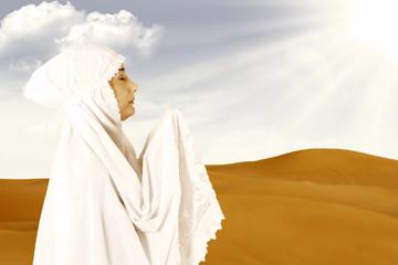 Female muslim in white praying at desert