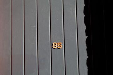numéro 85 sur façade de bois peinte en gris