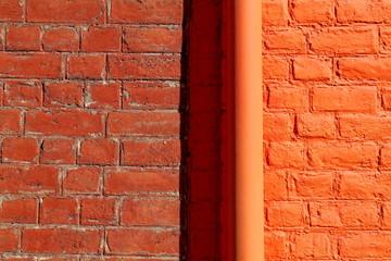 Mur de brique rouge et orange avec gouttière