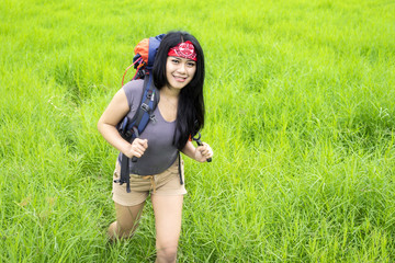 Female hiker walking in countryside meadow