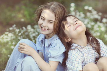 Two cute girls laughing on a beautiful summer meadow